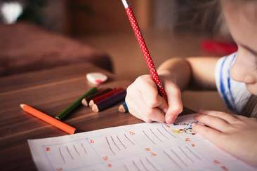 Student filling workbook with pencil as we answer your questions on Adventist Education - AAAF