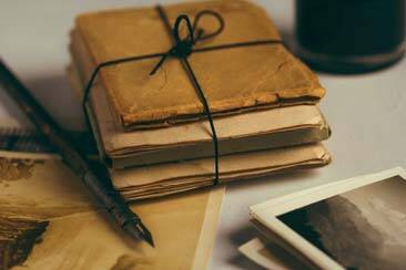 Parchment books tied in black ribbon, next to fountain ink pen and pictures of nature - AAAF